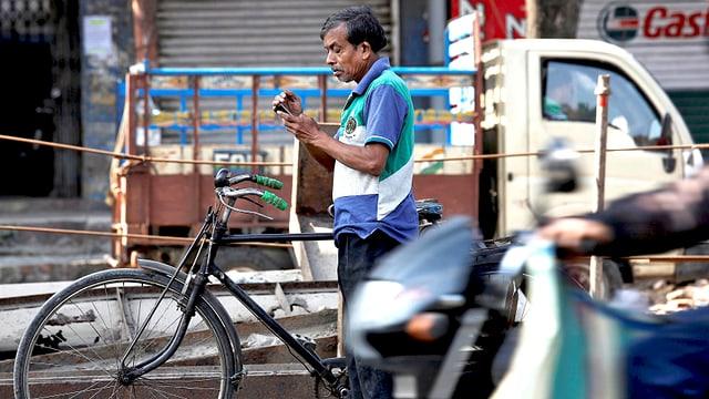 Inder mit Fahhrad am Strassenrand, in den Händen hält er ein Smartphone.
