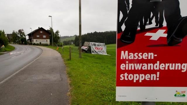 Plakat «Masseneinwanderung stoppen», dahinter Wiese, Strasse und ein Haus.