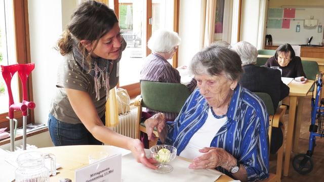 Etha Varone serviert einer Frau Glacé.