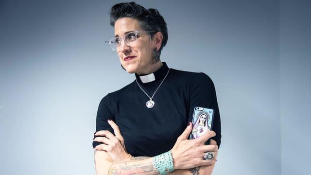 Eine Frau mit Kurzhaarschnitt und Tattoos hält ein Smartphone in der Hand. Sie ist Pfarrerin und trägt ein schwarzes T-Shirt, am Hals ist eine weisse Pfarrersbinde und eine Goldkette.