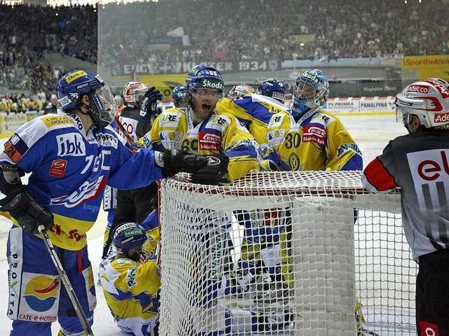 Klotens Frédéric Rothen und die Davoser Sandro Rizzi und Leonardo Genoni schauen zum Referee.
