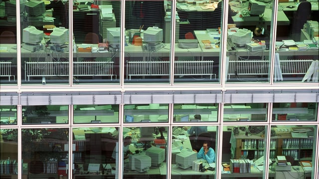 Einblick in ein Grossraumbüro durch eine Fensterfront.