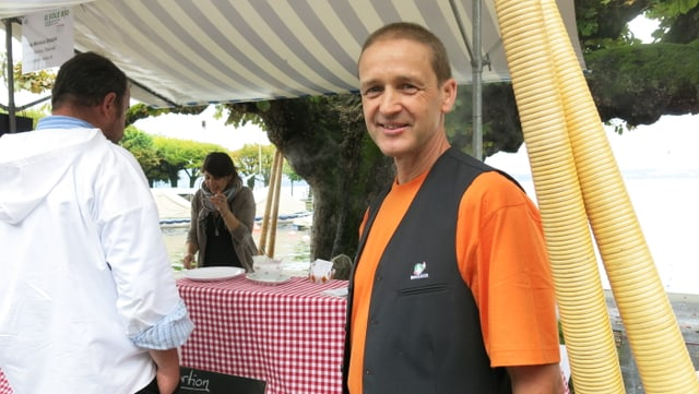 Bauer steht vor einem Marktstand am Bio Markt in Zug.