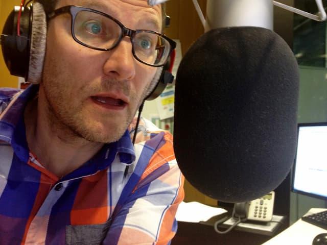 Toni Poltera mit Kopfhörern am Mikrofon im Radiostudio.