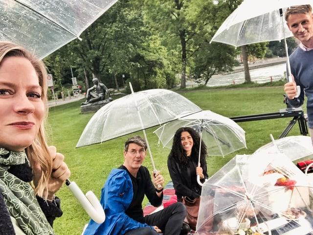 Franz Fischlin, Andrea Jansen, Peter Brönnimann und Mujinga Kambundji mit Regenschirmen sitzen auf einer Picknick-Decke in der Wiese.