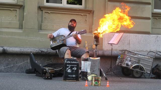 Ein Mann spielt Gitarre, vor ihm brennt eine Kaffeekanne.