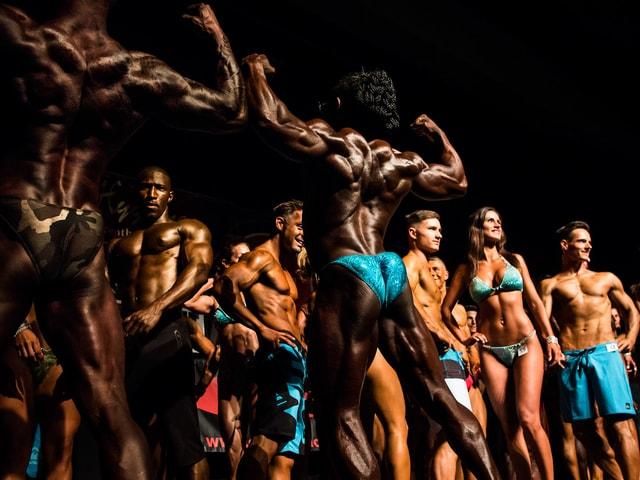 Männer und Frauen präsentieren auf der Bühne ihre Muskeln.