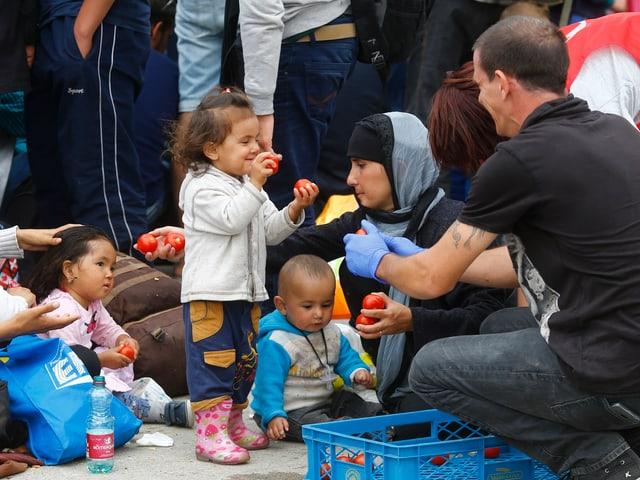 Helfer verteilt Äpfel an Flüchtlingskinder.