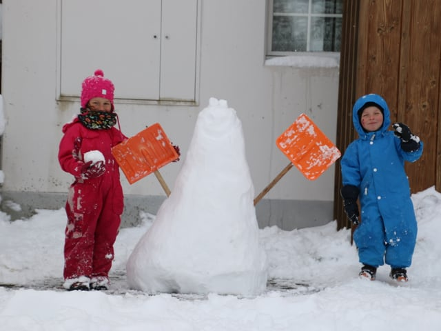 Zwei Kinder haben einen Schneemann gebaut.