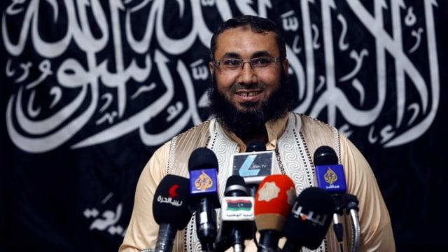 Ein bärtiger Mann mit Brille vor mehreren Mikrofonen, er lächelt, hinter ihm ein schwarzes Transparent mit arabischen Schriftzeichen.