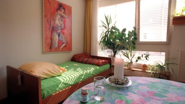 Zimmer mit Bett sowie Kerze und Medikament auf Tisch