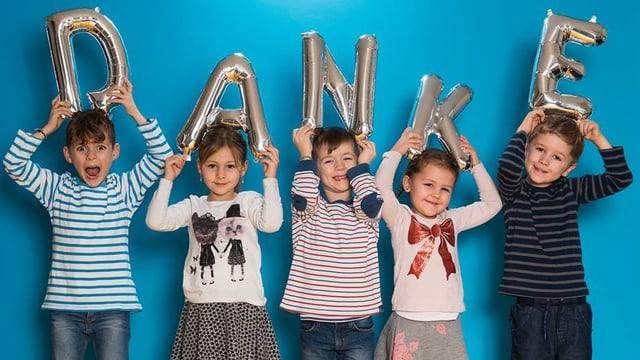 Fünf kleine Kinder mit den aufblasbaren Buchstaben D, A, N, K und E.
