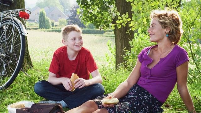 Ein Junge mit rotem T-Shirt sitzt neben einer Frau mit violettem T-Shirt im Gras.