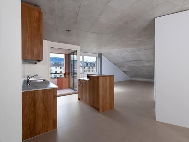 Blick in eine Küche mit dahinterliegendem Balkon.