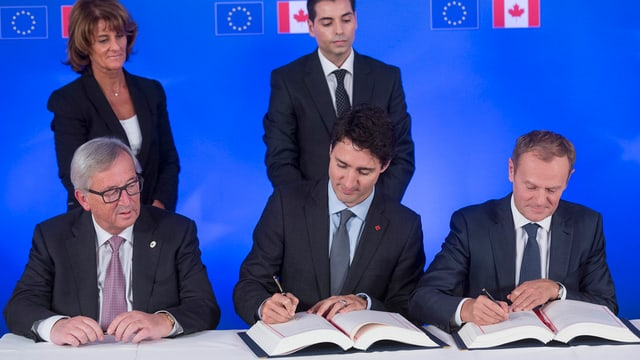 Purtret da Jean-Claude Juncker, Justin Trudeau e Donald Tusk.