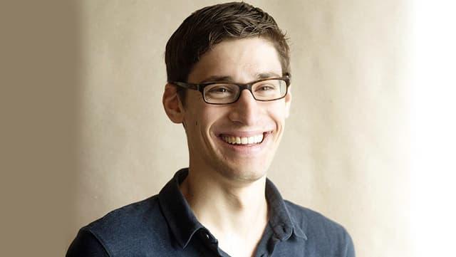 Junger Mann mit Brille lächelt in die Kamera