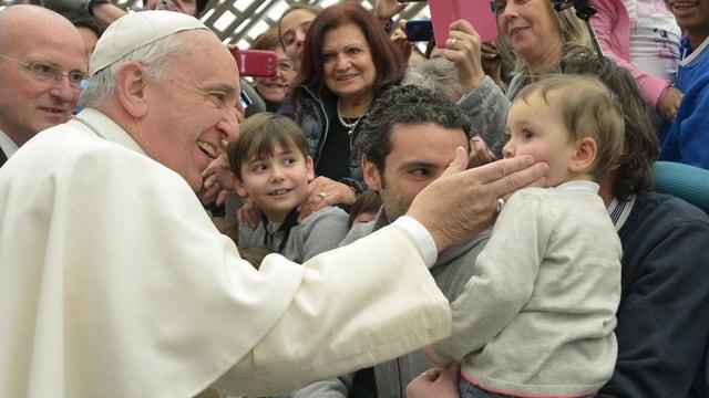 Papst Franziskus tätschelt einem Kind die Wange