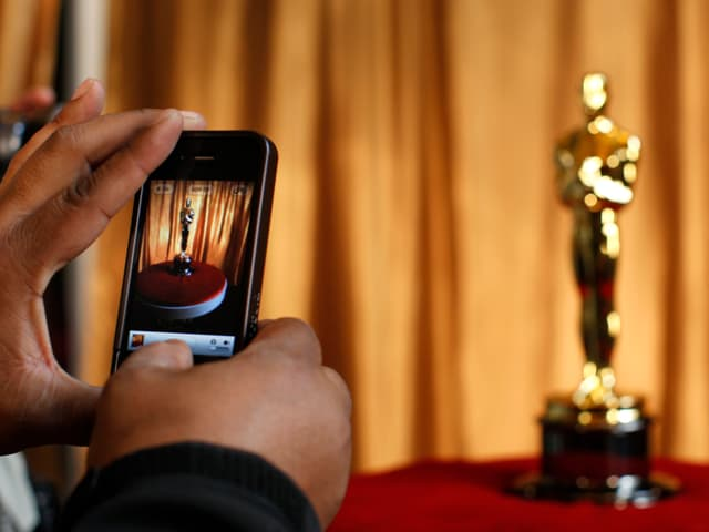 Zwei Hände halten ein Mobiltelefon, mit dem ein Foto einer goldenen Oscar-Statue geknippst wird.