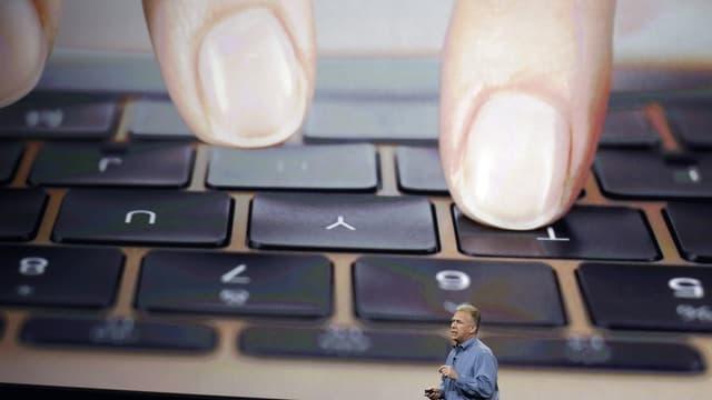 Kleiner Mann vor riesiger Tastatur mit gigantischen Fingerkuppen