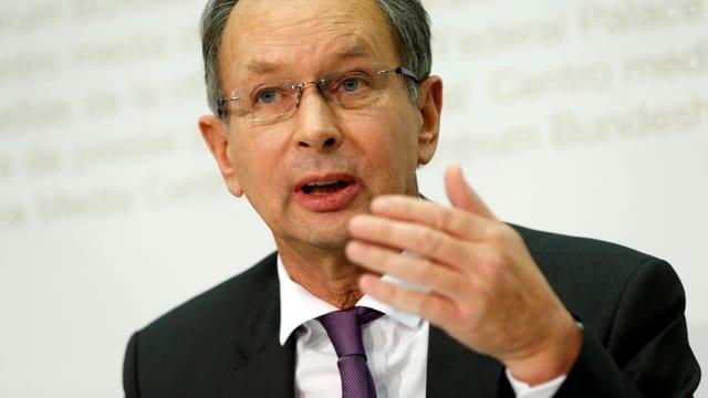 Müller mit schwarzem Sakko und violetter Krawatte im Brustbild, mit erhobener Hand und leicht vorgebeugt redend
