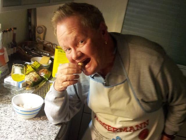Ein Mann mit Küchenschürze beisst fröhlich in eine Kartoffel aus Marzipan.