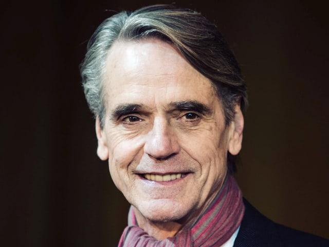 Ein älterer Herr mit  Halstuch, buschigen Augsbrauen und kurzem Haar; er lächelt.