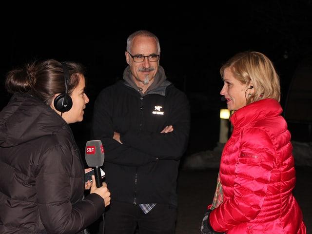 V.l.n.r: Patricia Banzer mit Mikrofon, Christian Peter und Sabine Dahinden in der Nacht.