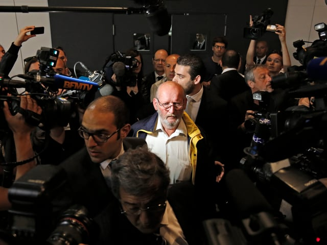 Der Hauptangeklagte Jean-Claude Mas in einer Schar von Journalisten.