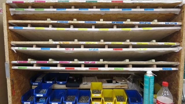 Holzgestell mit verschiedenen Schrauben und andern Metallteilen in Plastikbehältern.