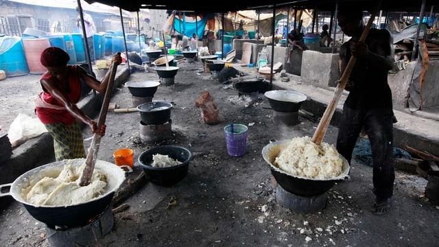 Eine Frau und ein Mann stampfen Maniok-Wurzeln auf einem Markt in Laos, Nigeria.
