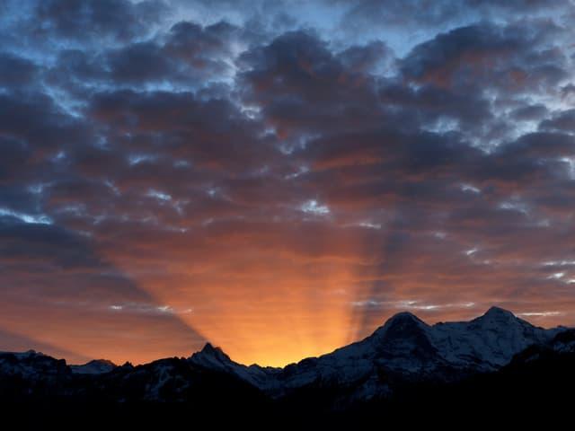 Unten schwarze Konturen der Berge, hinter den Gipfeln erste Sonnenstrahlen. Der Himmel ist leicht bewölkt.