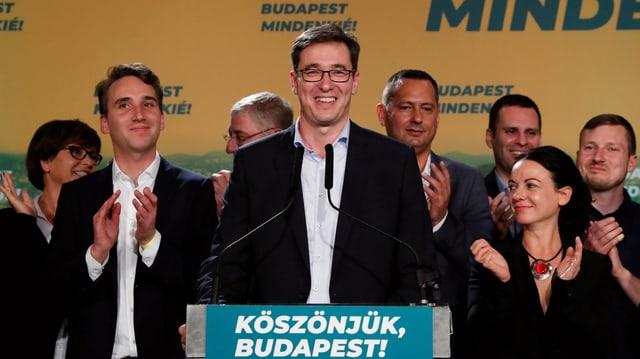 Gergely Karacsony lachend an einem Rednerpult.