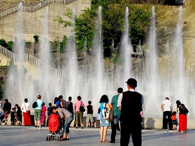 Eine Menschenmenge steht vor einer Brunnenanlage.