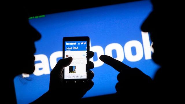 Ein Smartphone-Besitzer zeigt einem anderen die Facebook-App auf seinem Telefon.