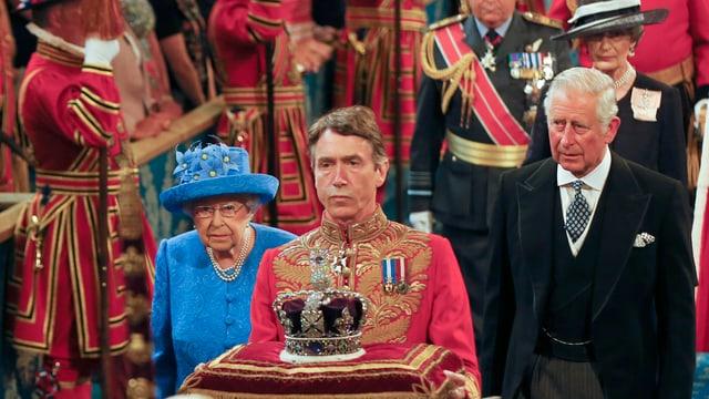 Queen geht neben ihren Sohn im Parlament. Vor ihr trägt ein Uniformierter die Krone.