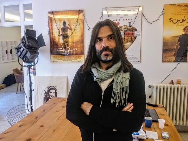 Khaled Mouzanar in seinem Büro, hinter ihm Filmplakate.