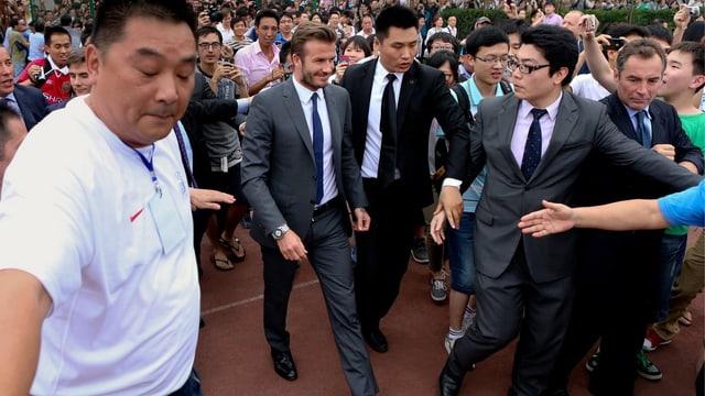 David Beckham läuft durch Shanghai, umzingelt von Sicherheitsleuten und einer riesigen Menschenmasse.