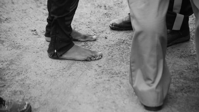 Die Füsse von zwei Menschen am Boden.