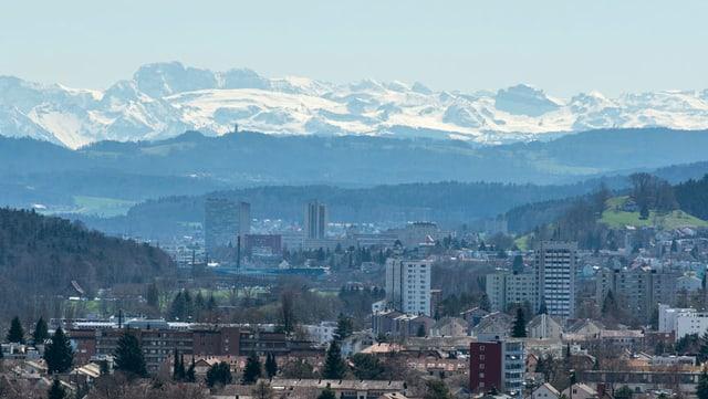 Blick auf eine Stadt, dahinter Hügel und Berge.