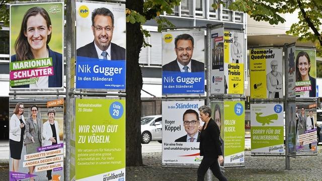Eine Frau läuft in Zürich an Plakaten für die eidgenössischen Wahlen 2019 vorbei.