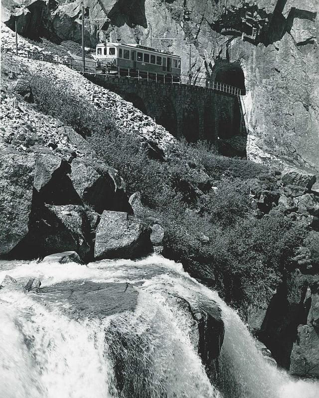 Historische Schwarzweiss-Aufnahme einer alten Eisenbahnbrücke mit kurzer Zugkomposition.