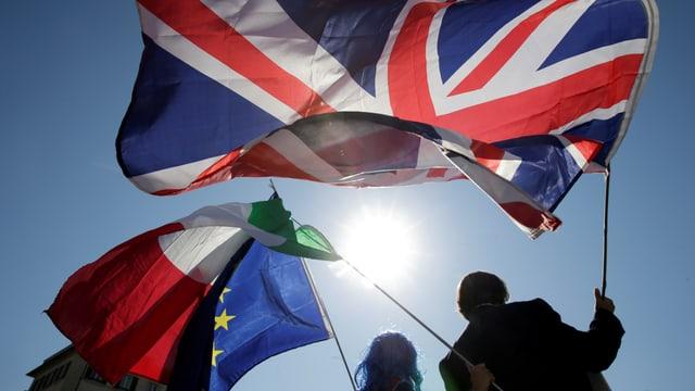 Leute schwingen GB-, Italien- und EU-Flaggen im Gegenlicht der Sonne.