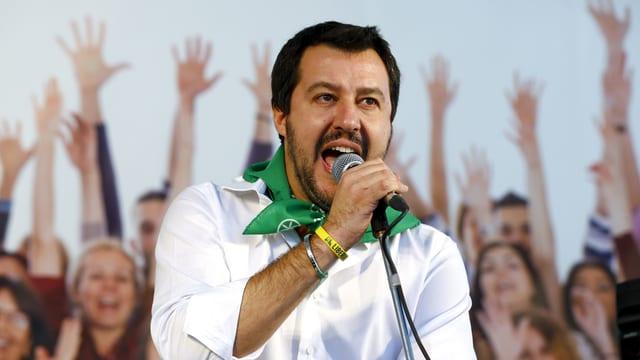 Salvini spricht in ein Mikrofon, im Hintergrund Anhänger, welche ihre Arme in die Luft strecken.