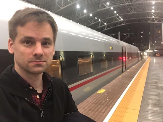 China-Korrespondent Martin Aldrovandi macht ein Selfie am Perron eines Chinesischen Bahnhofes. Hinter ihm steht ein grauer chinesischer Schnellzug mit roten Streifen auf der Seite.