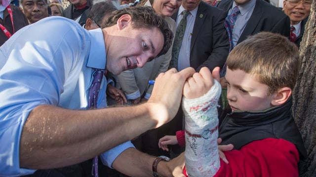 Justin Trudeau gibt ein Autogramm auf einen Gips eines Jungen.