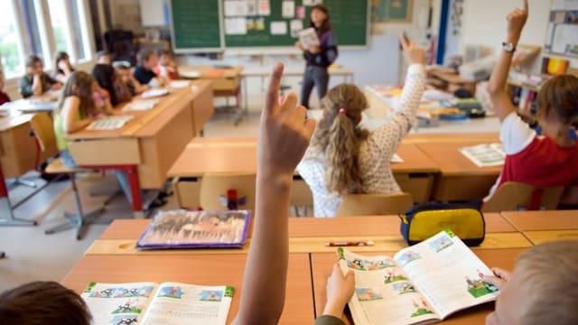 Schüler in einer Schulklasse strecken auf