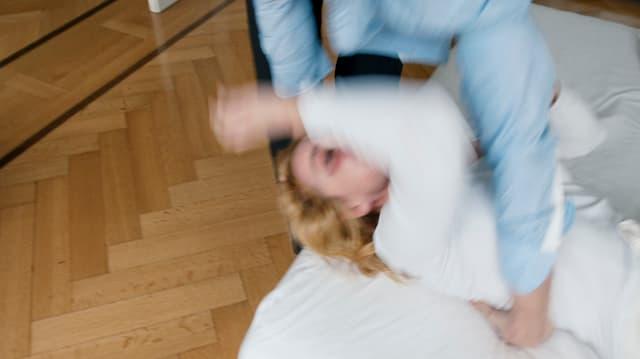 Ein Mann wirft eine Frau auf den Boden