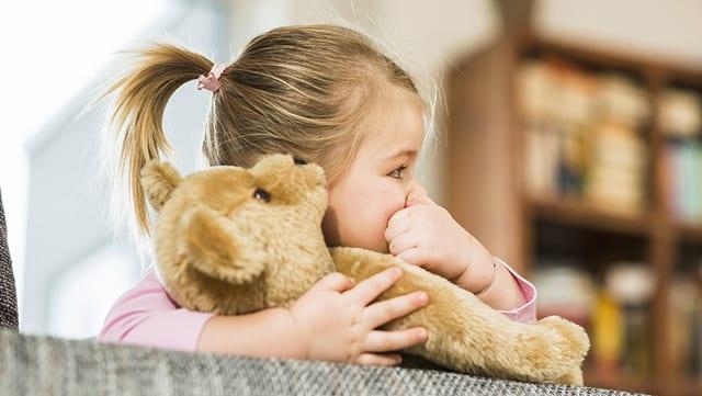 Mädchen hält Teddybär fet
