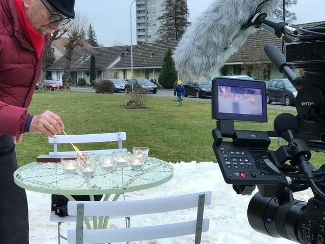 Ein Mann zündet Kerzen auf einem Tisch an