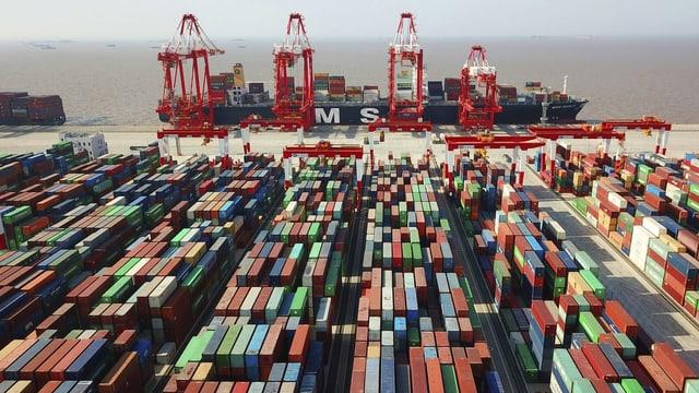 Auf dem Bild sind hunderte farbige Container zu sehen. Im Hintergrund ein Frachtschiff.